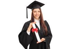 Vrouwelijke gediplomeerde student die een diploma houden stock afbeeldingen