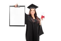Vrouwelijke gediplomeerde student die een klembord houden Royalty-vrije Stock Afbeelding