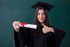 Vrouwelijke gediplomeerde student voor groene raad stock fotografie