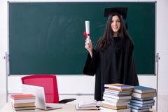 Vrouwelijke gediplomeerde student voor groene raad stock foto