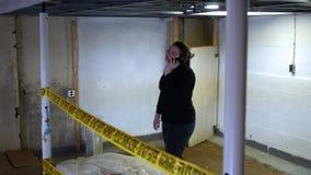 Vrouwelijke geheime politieman die vraag 911 maken bij moordscène stock video