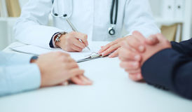 Vrouwelijke geneeskunde artsenhand die zilveren pen houden die iets op klembordclose-up schrijven Royalty-vrije Stock Foto