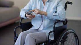Vrouwelijke gepensioneerde die in rolstoel Internet op smartphone, mededeling doorbladeren stock video
