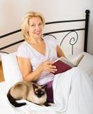 Vrouwelijke gepensioneerde met het boek van de kattenlezing Stock Foto's