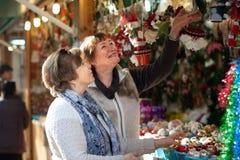 Vrouwelijke gepensioneerden die Kerstmisdecoratie kopen bij markt Royalty-vrije Stock Afbeeldingen
