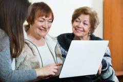 Vrouwelijke gepensioneerden en relatief het doorbladeren Web op laptop Stock Afbeeldingen