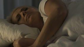 Vrouwelijke gepensioneerdeslaap in bed en het lijden aan rugpijn, gezondheidsproblemen stock video