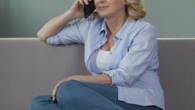 Vrouwelijke gepensioneerdezitting op bank, die gesprek over telefoon, vraag aan vriend hebben stock videobeelden
