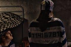 Vrouwelijke gevangene die gevangenis eenvormig met genaaide aantalvervanger dragen Stock Fotografie