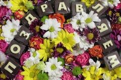 Vrouwelijke Giftachtergrond met een verscheidenheid van kleurrijke bloemen en chocoladeinschrijving in Russische gelukwensen Hoog Stock Afbeeldingen