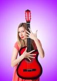 Vrouwelijke gitaarspeler tegen de gradiënt Stock Afbeelding