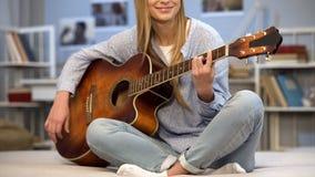 Vrouwelijke gitarist die lied uitvoeren thuis, creatieve hobby, die voor auditie voorbereidingen treffen stock fotografie