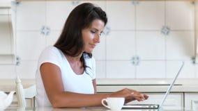 Vrouwelijke glimlachende onderneemster die van huis in keuken werken die laptop het drinken van PC thee of koffie gebruiken stock footage