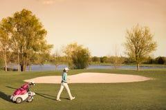 Vrouwelijke golfspeler die op fairway bij schemer lopen Royalty-vrije Stock Foto's