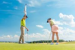 Vrouwelijke golfspeler klaar om de bal onder de instructie van een golfleraar te raken royalty-vrije stock foto