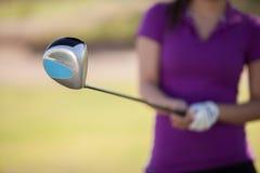 Vrouwelijke golfspeler klaar te slingeren Royalty-vrije Stock Afbeeldingen