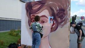 Vrouwelijke graffitikunstenaar die een portret trekken stock footage