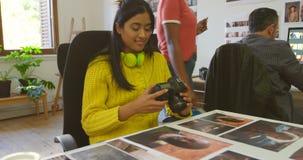 Vrouwelijke grafische ontwerper die foto's 4k bekijken stock videobeelden