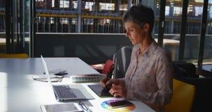 Vrouwelijke grafische ontwerper die grafiektablet gebruiken bij bureau 4k stock video