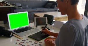 Vrouwelijke grafische ontwerper die grafiektablet gebruiken bij bureau 4k stock footage