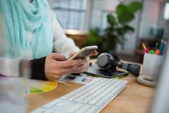 Vrouwelijke grafische ontwerper die mobiele telefoon met behulp van bij bureau Stock Fotografie