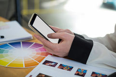 Vrouwelijke grafische ontwerper die mobiele telefoon met behulp van bij bureau Royalty-vrije Stock Foto's