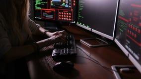 Vrouwelijke hakker die aan een computer werken, die bij nacht coderen stock video