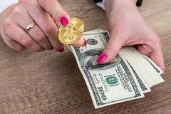 Vrouwelijke hand bitcoin en greepdollar die tonen royalty-vrije stock foto