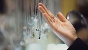 Vrouwelijke in hand de gemtegenhanger van de kopersholding, dure juwelententoonstelling, aankoop stock videobeelden