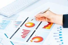 Vrouwelijke hand die aan de financiële de groeigrafiek richt Stock Foto's