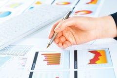 Vrouwelijke hand die aan de financiële de groeigrafiek richten Royalty-vrije Stock Afbeeldingen