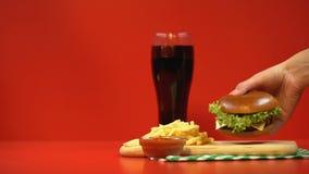 Vrouwelijke hand die aan hamburger, verleiding door snel voedsel lopen, het ongezonde eten stock video