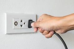 Vrouwelijke hand die aan het stoppen in toestel aan elektroafzet proberen Stock Afbeeldingen