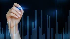 Vrouwelijke hand die abstracte financi?le grafieken trekken op onscherpe Blauwe donkere achtergrond Kaarsenforex grafiek royalty-vrije stock afbeeldingen