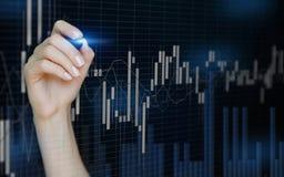 Vrouwelijke hand die abstracte financi?le grafieken trekken op onscherpe Blauwe donkere achtergrond Kaarsenforex grafiek royalty-vrije stock afbeelding