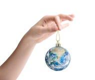 Vrouwelijke hand die de aarde houden als Kerstmisstuk speelgoed Elementen van dit die beeld door NASA wordt geleverd Stock Foto