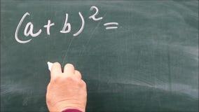 Vrouwelijke hand die de eerste binomiale formule op een bord schrijven stock footage