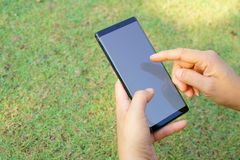 Vrouwelijke hand die de smartphonezwarte houden Stock Afbeeldingen