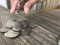 Vrouwelijke hand die de stapel van het geldmuntstuk zetten Stock Afbeelding