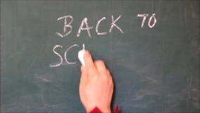 Vrouwelijke hand die de tekst terug naar school op een bord schrijven en een smiley trekken onder de woorden stock footage