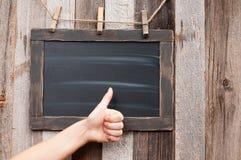 Vrouwelijke hand die duimen op schoolbord tonen stock afbeeldingen