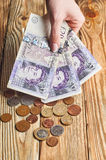Vrouwelijke hand die een Brits geld houden stock afbeeldingen