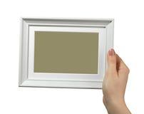 Vrouwelijke hand die een houten die kader houden op witte achtergrond wordt geïsoleerd Royalty-vrije Stock Fotografie
