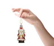 Vrouwelijke hand die een Kerstmisstuk speelgoed houden die op witte achtergrond wordt geïsoleerd Stock Fotografie