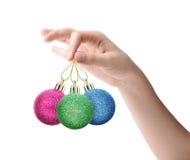 Vrouwelijke hand die een Kerstmisstuk speelgoed houden die op witte achtergrond wordt geïsoleerd Stock Afbeeldingen