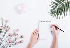 Vrouwelijke hand die in een notitieboekje bij het bureau, hoogste mening schrijven Royalty-vrije Stock Foto's