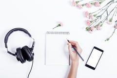 Vrouwelijke hand die in een notitieboekje, een mobiele telefoon, een hoofdtelefoon en een flo schrijven Royalty-vrije Stock Afbeelding