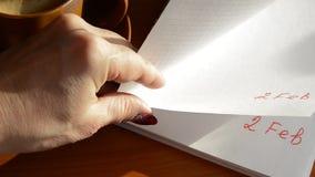 Vrouwelijke hand die een notitieboekje met dubbele datum doorbladeren - 2 Februari stock footage