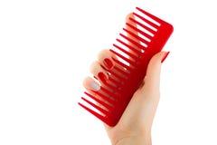 Vrouwelijke hand die een rode kam op een witte achtergrond houden stock fotografie
