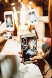 Vrouwelijke hand die een smartphone houden tegen close-up van beeldjepaar op huwelijkscake stock afbeeldingen